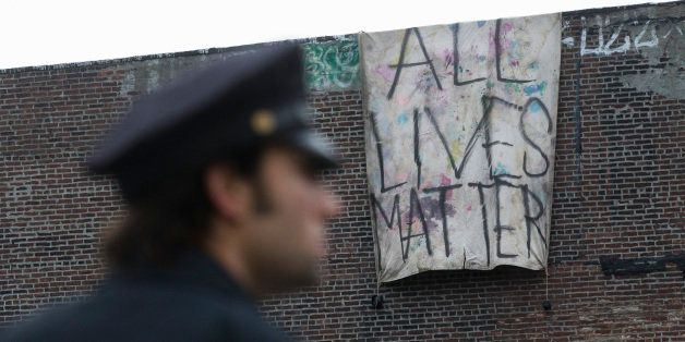 "A sign that reads ""ALL LIVES MATTER"" is hung from a building near a makeshift memorial at the site where NYPD officers Rafael"