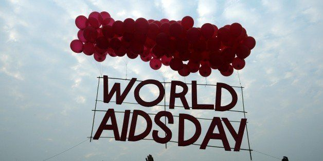 Indian social activists and children release a World AIDS Day awareness sign tied with ballons in Kolkata on December 1, 2015