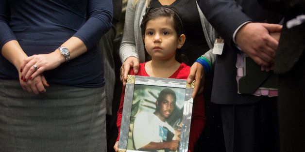 WASHINGTON, DC - DECEMBER 10: Caitlin Aguilar, 6, holds a photo of Teshawn Samuel, 18, who was shot by four assailants while