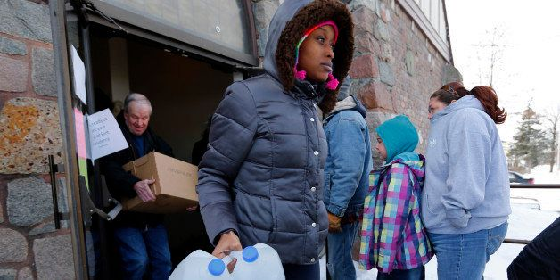 In this Tuesday, Feb. 3, 2015 photo, Genetha Campbell carries free water being distributed at the Lincoln Park United Methodi
