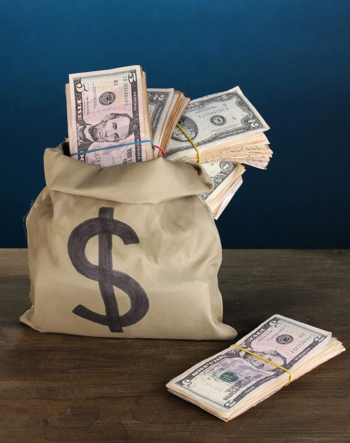 bag with stacks of dollars on...
