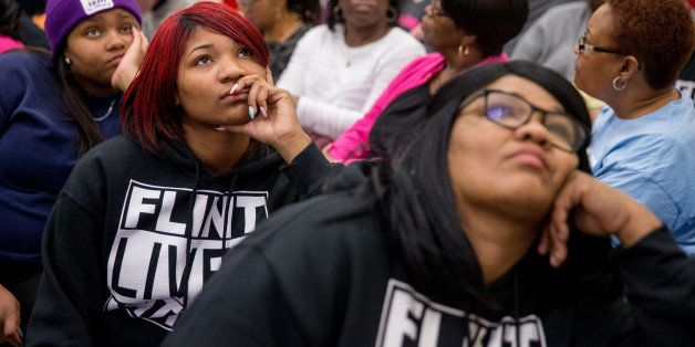 """Lisia Williams, right, and her daughter Jada, second from left, wear shirts that read """"Flint Lives Matter"""" as they join fello"""