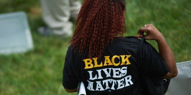 A woman wears a shirt with 'Black Lives Matter' during a memorial service for slain 18 year-old Michael Brown Jr. on August 9