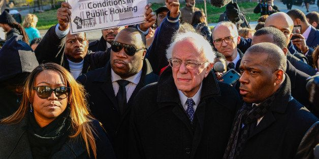 U.S. Democratic presidential candidate Sen. Bernie Sanders (I-VT) walks with Pastor Jamal Bryant (R) and local clergy near th