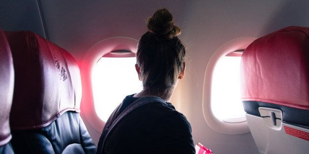 Woman Looking Through Window While Traveling In Airplane