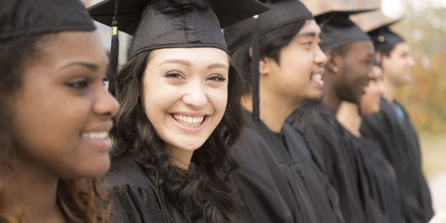 Six multi-ethnic friend graduates excitedly wait for their name to be called during graduation ceremony. Mixed-race girl look