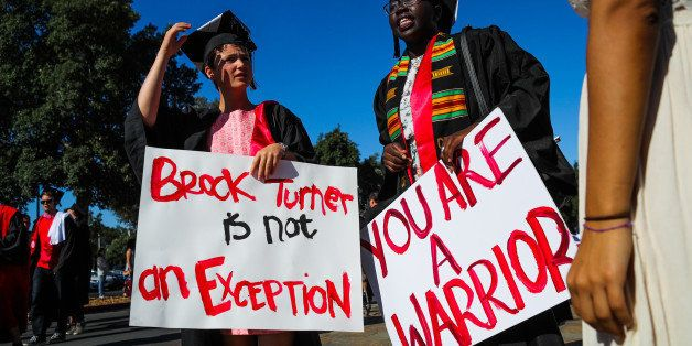 Stanford students Miriam Natvig (L) and Jemima Oslo (R) carried signs in solidarity for a Stanford rape victim during graduat