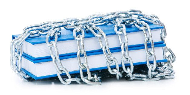 Censorship concept with books and chains on white