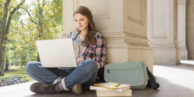 College student studying with laptop and earbuds