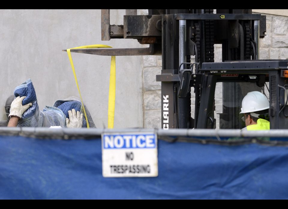 Workers handle the statue of former Penn State football coach Joe Paterno before removing the statue Sunday, July 22, 2012, i