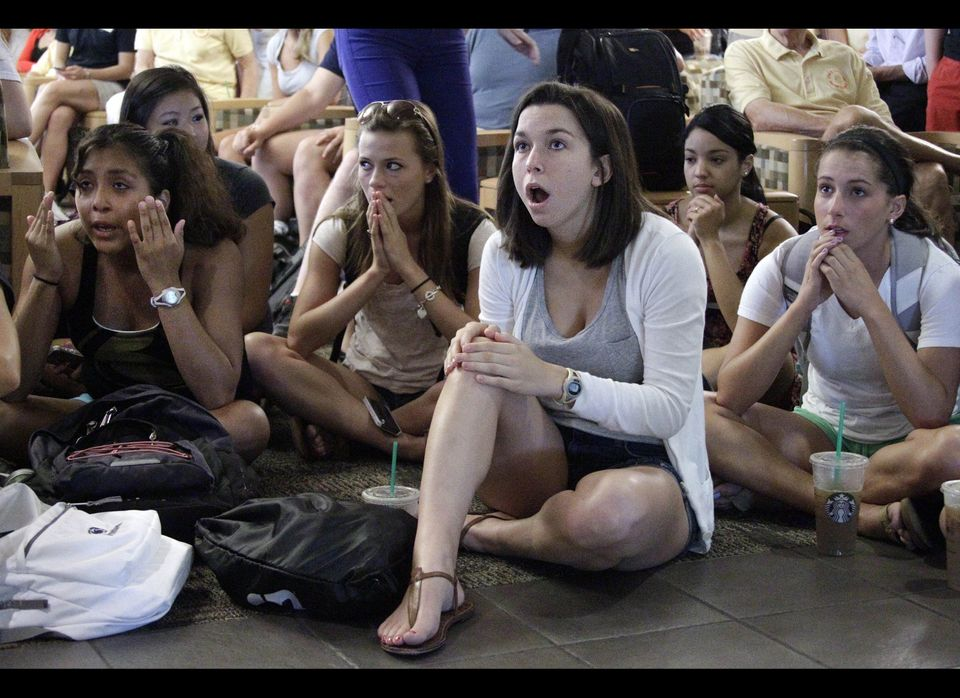 Laura Lovins, a Penn State University sophomore from State College, Pa., center, reacts while listening to a television in th
