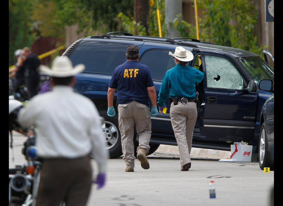 ATF and other investigators walk near a vehicle which was struck by a bullet near the scene where a gunman opened fire near t