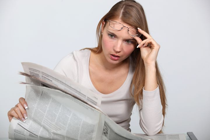 woman shocked by newspaper...