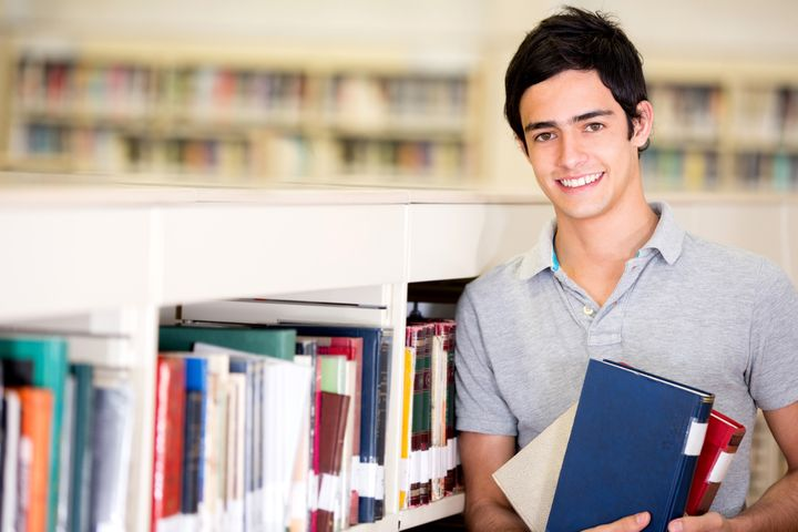 happy male student holding...