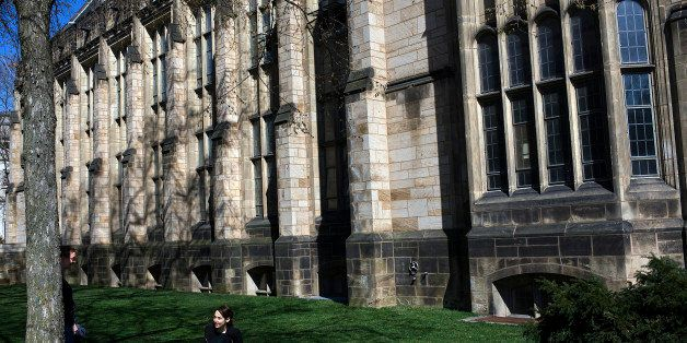 NEW HAVEN, CT - APRIL 15:  A woman sits on the grass on the campus of Yale University April 15, 2008 in New Haven, Connecticu