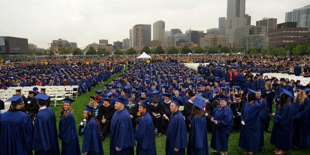 Graduates line up to receive their diplomas under cool and cloudy skies with the skyline of Denver as their backdrop. Metropo