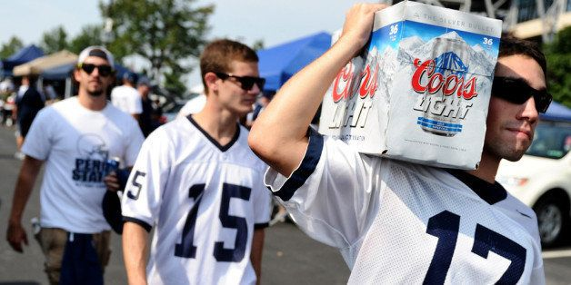 STATE COLLEGE, PA - SEPTEMBER 01: Penn State tailgaters walks with beer in the parking lot prior to the Penn State Nittany Li