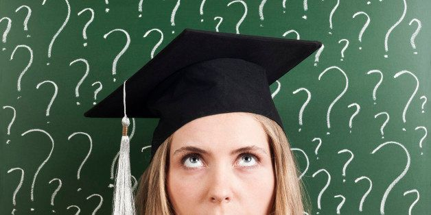 young woman student wearing cap in front of question marks written blackboard and thinking about her future