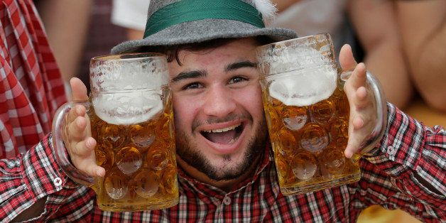 A young man poses with beer mugs at the second weekend in the 'Hofbraeuhaus beer tent' at the famous beer festival Oktoberfes