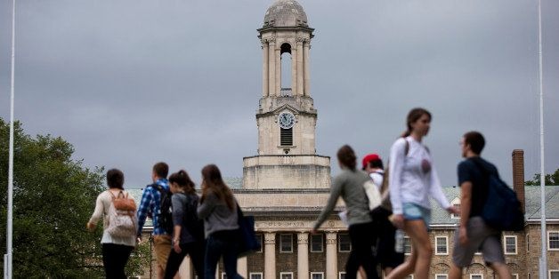 Students walk past the Old Main building on the Penn State campus Tuesday, Sept. 9, 2014, in State College, Pa. Penn State fo