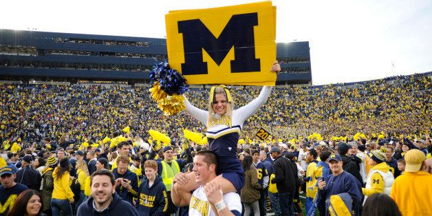 ANN ARBOR, MICHIGAN - NOVEMBER 26, 2011: A cheerleader from the University of Michigan is carried around on the shoulders of