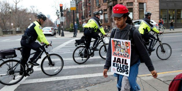 Boston Arts Academy student, Michael Cordero, 18, walks as police ride by on bicycles during a march in Boston, Monday, Dec.