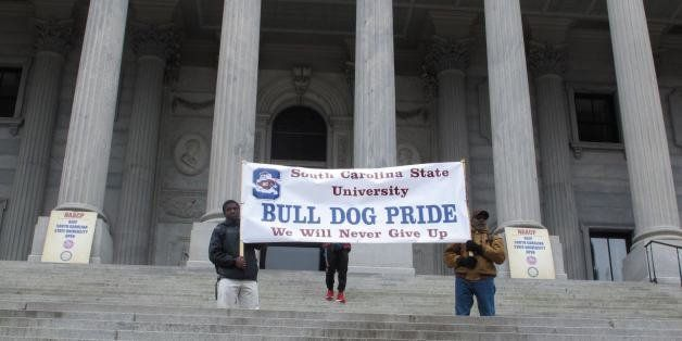 Supports of South Carolina State University hold up a banner at a Statehouse rally against against a proposal to close South