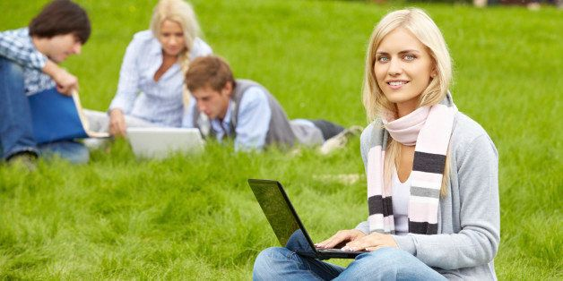 'Beautiful girl studying with laptop on grass, looking at camera and smiling'