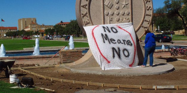 """Texas Tech freshman Regan Elder helps drape a bed sheet with the message """" No means No,"""" over the university's seal on the Lu"""