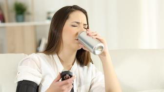 Woman suffering a low blood pressure drinking sweet soda sitting on a couch in the living room at home