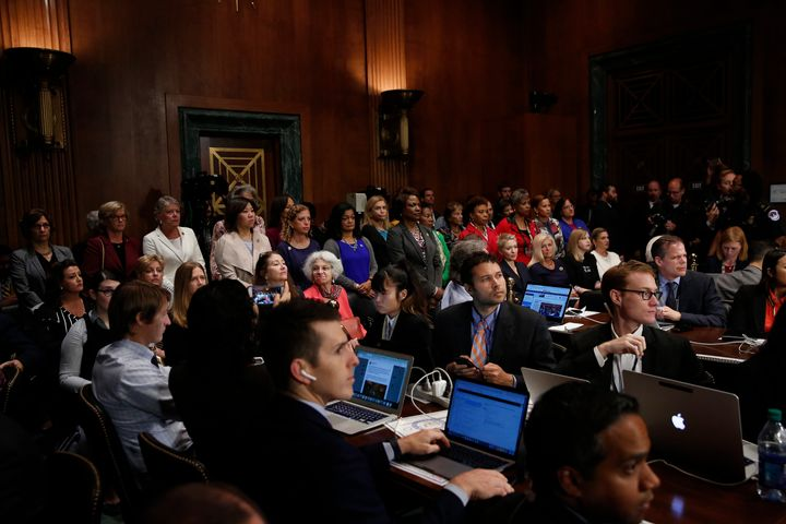 Female members of the House of Representatives stand up to protest during a Senate Judiciary Committee meeting September 28,