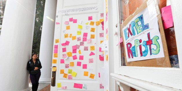 A University of Virginia student looks over postings on the door of Peabody Hall related to the Phi Kappa Psi gang rape alleg