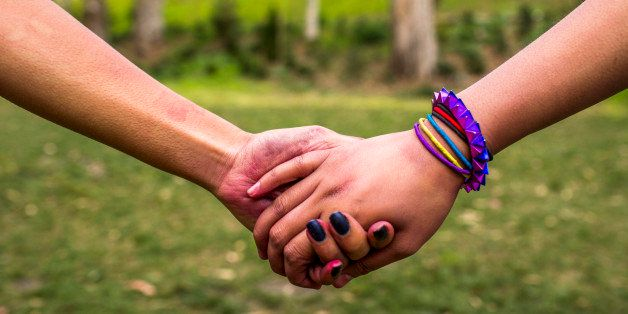 Close up of women holding hands in park