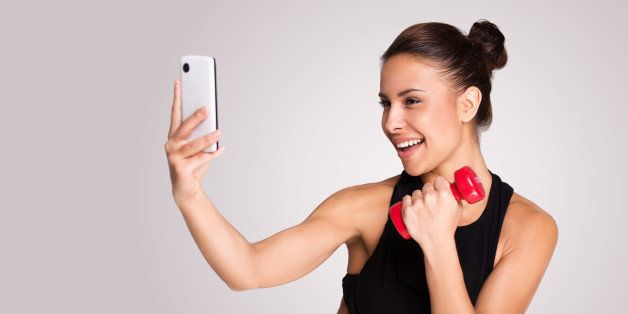 Young mixed race woman making selfie while taking fitness exercises, standing on grey background