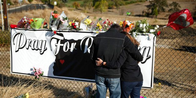 Charley Thompson, left, and his wife Rachel Thompson embrace as they place flowers at a makeshift memorial near the road lead