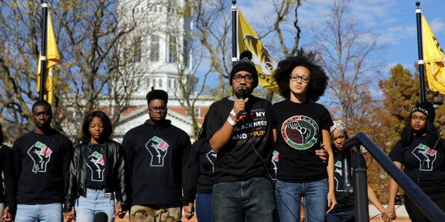 FILE - In this Nov. 9, 2015, file photo, graduate student Jonathan Butler, center, addresses a crowd following the announceme