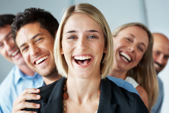 Portrait of a happy young female business leader stading in front of her team