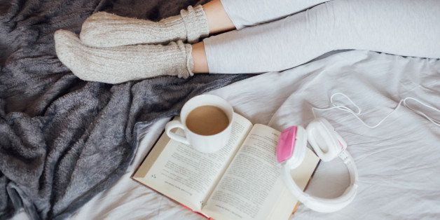 Women resting leg in bad enjoing in reading book, drinking coffee and listening music.