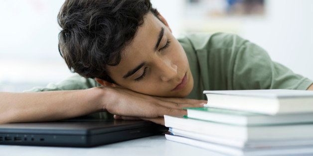 Male high school student napping at desk