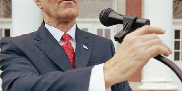 Mature Businessman at lectern outdoors, holding microphone and documents