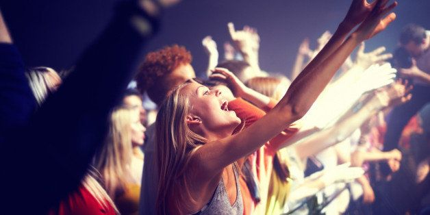 A group of people standing with their arms raised at a concert. This concert was created for the sole purpose of this photo s