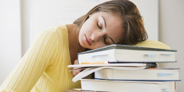 Tired Indian student laying on stack of textbooks