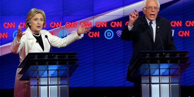 Democratic U.S. presidential candidates Hillary Clinton (L) and Senator Bernie Sanders speak simultaneously during a Democrat