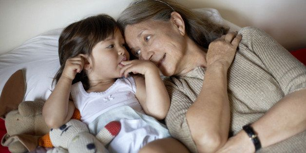 Grandmother and granddaughter (2-3) lying on bed, elevated view