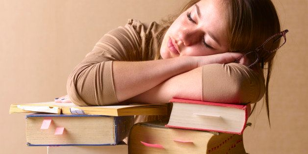 University student falling asleep on text books