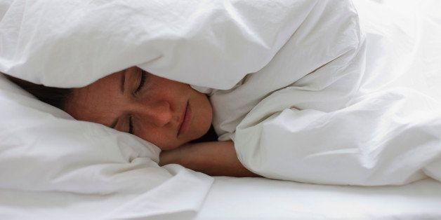 Sick woman sleeping in bed under blanket
