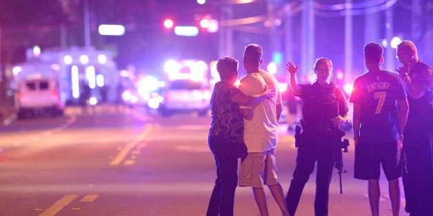 Orlando Police officers direct family members away from a fatal shooting at Pulse Orlando nightclub in Orlando, Fla., Sunday,