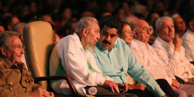 TOPSHOT - In this handout picture released by Prensa Miraflores, former Cuban President Fidel Castro (2nd L), sitting between