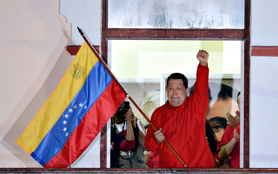 Venezuelan President Hugo Chavez waves a Venezuelan flag while speaking to supporters after receiving news of his reelection