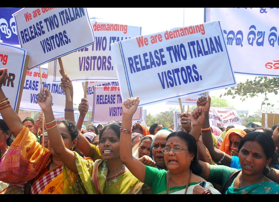 Indian women hold placards demanding the release of two abducted Italians, Paolo Bosusco and Claudio Colangelo, at a rally in